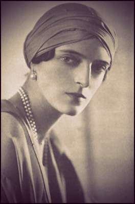 Irina Yusupova wearing a turban, pearl earrings, and a double stranded pearl necklace.
