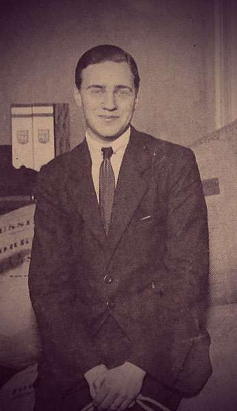 Photo of Nikita Romanov - he's smiling and wearing a dark suit and tie.